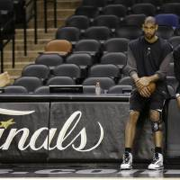 Photo - San Antonio Spurs' Tim Duncan, left, and guard Tony Parker, right, of France, talk during a practice, Wednesday, June 12, 2013, in San Antonio. San Antonio will face the Miami Heat in game 4 of the NBA Finals basketball game Thursday. San Antonio leads the best-of-seven series 2-1.     (AP Photo/Eric Gay)