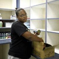 Photo - Midwest  City High School junior Meladee Cheadle stocks  food in a  pantry at  Oklahoma Youth Services in  Oklahoma  City, Thursday July, 23, 2009. Photo by Sarah Phipps