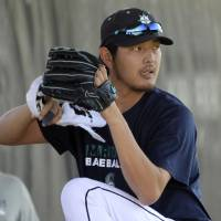 Photo - Seattle Mariners pitcher Hisashi Iwakuma of Japan works out with staff in the bullpen using a towel in his throwing hand during a morning workout at spring training baseball practice, Wednesday, March 5, 2014, in Peoria, Ariz. (AP Photo/Tony Gutierrez)