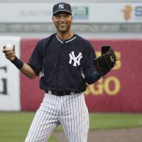 Photo - New York Yankees Derek Jeter laughs as he throws in the rain before a spring exhibition baseball game against the Miami Marlins was canceled due to the weather in Tampa, Fla., Saturday, March 29, 2014. (AP Photo/Kathy Willens)