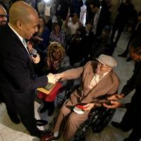Photo - Newark Mayor Cory Booker, left, shakes hands with Willie Wilkins after returning a box with Wilkins World War II dog tags, which he lost in France during the war, at an event to return them to the veteran, Wednesday, May 8, 2013, in Newark, N.J. The U.S. Army tags were lost in 1944 and were found by Anne-Marie Crespo, a resident of Istres, France, who was digging in her garden in 2001. The event, which was held as a surprise for Wilkins, 90, also marked the 68th anniversary of V-E Day, the end of World War II in Europe. (AP Photo/Julio Cortez)