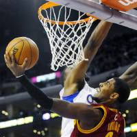 Photo -   Cleveland Cavaliers guard Kyrie Irving (2) shoots a layup around Los Angeles Clippers center DeAndre Jordan, rear, in the first half of an NBA basketball game, Monday, Nov. 5, 2012, in Los Angeles. (AP Photo/Gus Ruelas)