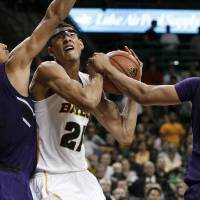 Photo - Northwestern's Jared Swopshire (12) and Mike Turner (10) combine to stop a drive to the basket by Baylor's Isaiah Austin (21) in the second half of an NCAA college basketball game Tuesday, Dec. 4, 2012, in Waco, Texas. Northwestern defeated Baylor 74-70. (AP Photo/Tony Gutierrez) ORG XMIT: TXTG111