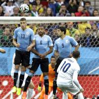 Photo - England's Wayne Rooney tries to get the ball over the Uruguay defensive wall on a free kick during the group D World Cup soccer match between Uruguay and England at the Itaquerao Stadium in Sao Paulo, Brazil, Thursday, June 19, 2014.  (AP Photo/Kirsty Wigglesworth)