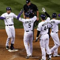 Photo - From left, Colorado Rockies' Nolan Areando, left, is congratulated by teammates Carlos Gonzalez, Ryan Wheeler and Troy Tulowitzki as he steps on home plate after hitting a grand slam against the New York Mets in the fifth inning of a baseball game in Denver, Saturday, May 3, 2014. (AP Photo/David Zalubowski)