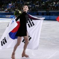 Photo - Yuna Kim of South Korea, left, and Adelina Sotnikova of Russia skate on the ice following the flower ceremony for the women's free skate figure skating finals at the Iceberg Skating Palace during the 2014 Winter Olympics, Thursday, Feb. 20, 2014, in Sochi, Russia. Sotnikova placed first, followed by Kim and Kostner. (AP Photo/Bernat Armangue)