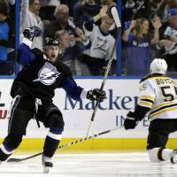 Photo -   Tampa Bay Lightning's Steven Stamkos, left, celebrates after scoring a goal as Boston Bruins' Johnny Boychuk (55) looks on during the third period in Game 6 of an NHL hockey Stanley Cup playoffs Eastern Conference final series in Tampa, Fla., Wednesday, May 25, 2011. (AP Photo/Chris O'Meara)