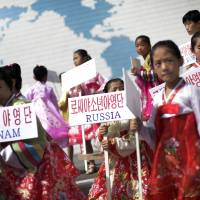 Photo - Young North Korean girls hold up signboards with the names of participating countries during an opening ceremony at the Songdowon International Children's Camp, Tuesday, July 29, 2014, in Wonsan, North Korea. The camp, which has been operating for nearly 30 years, was originally intended mainly to deepen relations with friendly countries in the Communist or non-aligned world. But officials say they are willing to accept youth from anywhere - even the United States.  (AP Photo/Wong Maye-E)