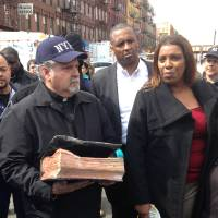 Photo - Rick Del Rio, pastor of Abounding Grace church in Manhattan, and New York City Public Advocate Letitia James, display a damaged but intact Bible they said was recovered in the rubble of the Spanish Christian Church, Saturday, March 15, 2014 in New York. The church was in one of the buildings destroyed in the March 12 gas explosion that leveled two building and killed eight people. (AP Photo/Jim Fitzgerald)