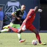 Photo - Seattle Sounders player Clint Dempsay, left, vies for the ball against Portland Timbers goalie Donovan Ricketts during an MLS soccer game in Portland, Ore., Sunday, Aug. 24, 2014. (AP Photo/Natalie Behring)
