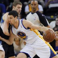 Photo - Golden State Warriors' Klay Thompson (11) drives for the basket against Minnesota Timberwolves' Luke Ridnour during the first half of an NBA basketball game, Tuesday, April 9, 2013, in Oakland, Calif. (AP Photo/George Nikitin)