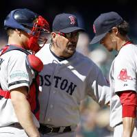 Photo -   Boston Red Sox pitching coach Randy Niemann, center, talks with catcher Ryan Lavarnway, left, and starting pitcher Clay Buchholz in the fouth inning of a baseball game against the Seattle Mariners, Monday, Sept. 3, 2012, in Seattle. (AP Photo/Elaine Thompson)