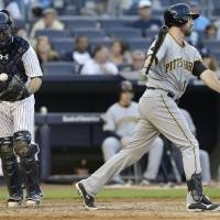 Photo - New York Yankees catcher Brian McCann, left, pops the ball out of his glove after Pittsburgh Pirates first baseman Ike Davis (15) swung and missed for strike three to end the top of the eighth inning of a baseball game, Saturday, May 17, 2014, in New York. The Yankees won 7-1. (AP Photo/Julie Jacobson)