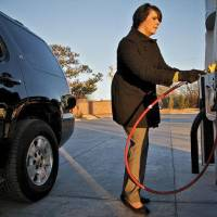 Photo - In this archive photo, Sundee Busby prepares to fill her Chevrolet Tahoe at a natural gas pump located at the OnCue Express on Jan. 11 in Edmond.  CHRIS LANDSBERGER - CHRIS LANDSBERGER