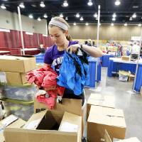 Photo - Julia Tucker, with OK Runner, unboxes running clothes Thursday at the Cox Convention Center in preparation for the marathon.