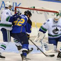 Photo - Vancouver Canucks' goalie Eddie Lack (31), of Sweden, blocks a shot by St. Louis Blues' David Backes (42) as Canucks' Ryan Stanton (18) defends during the second period of an NHL hockey game on Friday, Oct. 25, 2013, in St. Louis. (AP Photo/Bill Boyce)