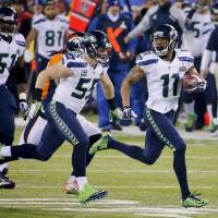 Photo - Seattle Seahawks wide receiver Percy Harvin (11) returns a kickoff for a touchdown against the Denver Broncos during the second half of the NFL Super Bowl XLVIII football game, Sunday, Feb. 2, 2014, in East Rutherford, N.J. (AP Photo/Matt York)