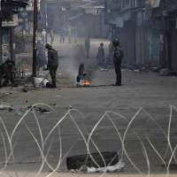 Photo - Indian policemen guard a residential area on the fourth consecutive day of curfew imposed after the execution of a Kashmiri man convicted in a deadly 2001 attack on India's Parliament in Srinagar, India, Tuesday, Feb. 12, 2013. Mohammed Afzal Guru was hanged in New Delhi early Saturday. Ahead of the execution, authorities had anticipated anti-India protests and ordered people in most of the Indian-held part of the disputed Kashmir region to remain indoors indefinitely. (AP Photo/Mukhtar khan)