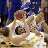 Photo - Iowa State' Hallie Christofferson, bottom, grabs a loose ball on the floor with help from teammate Brynn Williamson, top, against Kansas' Catherine Williams, center, in the second half of an NCAA college basketball game in the Big 12 women's tournament on Saturday, March 9, 2013, in Dallas. Iowa State won 77-62. (AP Photo/Tony Gutierrez)