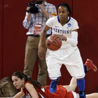 Photo - Kentucky's A'dia Mathies dribbles away from Dayton's Kelley Austria in the second half of a second-round game in the NCAA women's college basketball tournament Tuesday, March 26, 2013, in New York. Kentucky won 84-70. (AP Photo/Frank Franklin)