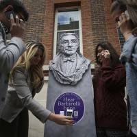 Photo - People listen to a talking statue on their phones at the launch of Talking Statues in central London, Tuesday Aug. 19, 2014. Statues of some three dozen historical and fictional characters in London and Manchester are coming to life thanks to a new interactive project that gives them a voice to tell their stories. Passers-by can swipe their smartphones on a tag or type in a web address to get an instant call from the characters depicted. Actors including Patrick Stewart and Downton Abbey's Hugh Bonneville perform the monologues, which lasts a few minutes each. (AP Photo/PA, Philip Toscano) UNITED KINGDOM OUT