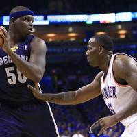 Photo - Memphis Grizzlies forward Zach Randolph (50) faces the basket as Oklahoma City Thunder center Kendrick Perkins (5) defends during the first quarter of Game 1 of the opening-round NBA basketball playoff series in Oklahoma City on Saturday, April 19, 2014. (AP Photo/Alonzo Adams)
