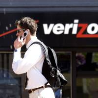 Photo - FILE - In this Monday, July 28, 2008, file photo, Eric Roden speaks on his cell phone as he walks past a Verizon store in Portland, Ore. Verizon says, Monday, Sept. 2, 2013, it has agreed to buy Vodafone's stake in Verizon Wireless for $130 billion. (AP Photo/Don Ryan, File)