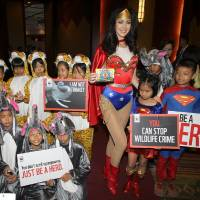 Photo - Miss Universe 2005 Natalie Glebova of Canada, center, wearing Wonder Woman costume poses with Thai children in elephant and tiger costumes on the occasion of Convention on International Trade in Endangered Species, or CITES, in Bangkok, Thailand Sunday, March 3, 2013. How to slow the slaughter and curb the trade in