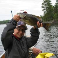 Photo - Declan Lawson, 10, of Moore is excited after catching a 4-pound smallmouth bass on Crooked Lake, Minn. Photo by Tyler Cotner