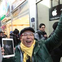 Photo -   FILE -In this Friday, Nov. 2, 2012, file photo, a customer, Song Tae-min reacts after buying a new iPad Mini in Seoul, South Korea. The tablet computer is without a doubt the gift of the year. just like it was last year. But if you resisted the urge in 2011, now is the time to give in. This season's tablets are better all around. Intense competition has kept prices very low, making tablets incredible values compared to smartphones and PCs (AP Photo/Ahn Young-joon)