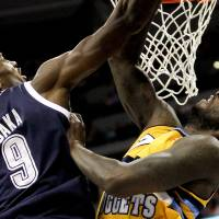 Photo - Oklahoma City Thunder's Serge Ibaka (9) and Denver Nuggets' J.J. Hickson (7) compete for a rebound during the first quarter of an NBA basketball game Thursday, Jan. 9, 2014, in Denver. (AP Photo/Barry Gutierrez)