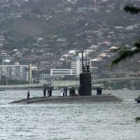 Photo - FILE - The submarine USS Greeneville is escorted to the submarine base at Pearl Harbor, in this Feb. 10, 2001, file photo. A high concentration of important military commands and facilities on the island mean there's a great deal of information in Hawaii that potential adversaries want to know. (AP Photo/Ronen Zilberman)