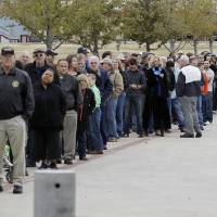 Photo - People wait in line to attend a memorial service for Christopher Kyle at Cowboys Stadium, Monday, Feb. 11, 2013, in Arlington, Texas. Thousands are expected to attend the public memorial service for Kyle, the former Navy SEAL sniper who was shot to death at a Texas shooting range. (AP Photo/Brandon Wade)