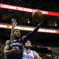 Photo - Memphis Grizzlies' Rudy Gay, left, drives to the basket past Philadelphia 76ers' Spencer Hawes (00) during the first half of an NBA basketball game, Monday, Jan. 28, 2013, in Philadelphia. (AP Photo/Matt Slocum)