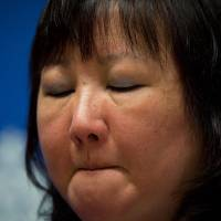 Photo - Carol Todd fights back tears as she listens during a Royal Canadian Mounted Police news conference in Surrey, British Columbia, on Thursday, April 17, 2014. A 35-year-old man alleged to be involved with the online extortion of Todd's 15-year-old daughter, who committed suicide in 2012, has been arrested in the Netherlands. (AP Photo/The Canadian Press, Darryl Dyck)