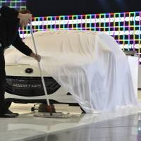 Photo - A worker cleans the floor next to a car at the Mazda booth during last preparations prior to the opening of the press preview days at the 83nd Geneva International Motor Show in Geneva, Switzerland, Saturday, March 2, 2013. The Motor Show will open its gates to the public from March 7 to 17, presenting more than 260 exhibitors and more than 130 world and European premieres. (AP Photo/Keystone, Martial Trezzini)