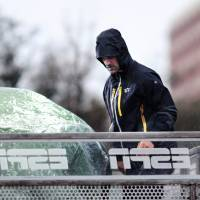 Photo - A staff worker of ESPN's traveling show College Gameday covers the shows' completed set up from the freezing rain on Friday afternnon. The show will broadcast Saturday morning, November 23, 2013 from Oklahoma State's library lawn. Photo by KT King/For the Oklahoman