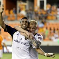 Photo - Real Salt Lake's Javier Morales, left, celebrates with Luke Mulholland, right, after scoring his third goal of the game against the Houston Dynamo during the second half of a MLS soccer game Sunday, May 11, 2014, in Houston. Real Salt Lake won 5-2. (AP Photo/David J. Phillip)
