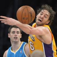 Photo - Los Angeles Lakers forward Pau Gasol, right, of Spain, reaches for a rebound as New Orleans Hornets forward Jason Smith looks on during the first half of an NBA basketball game, Tuesday, Jan. 29, 2013, in Los Angeles. (AP Photo/Mark J. Terrill)