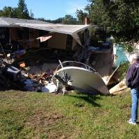 Photo - A man observes a sinkhole has swallowed parts of two houses in Dunedin, Fla. on Thursday, Nov. 14, 2013.   Dunedin Deputy Fire Chief Trip Barrs said the hole appeared to be about 12-feet wide when officials arrived on the scene. Residents of the neighboring houses also were evacuated as a precaution.  There are no reports of injuries. (AP Photo/The Tampa Tribune, Luke Johnson)  ST. PETERSBURG OUT; LAKELAND OUT; BRADENTON OUT; MAGS OUT; LOCAL TV OUT; WTSP CH 10 OUT; WFTS CH 28 OUT; WTVT CH 13 OUT; BAYNEWS 9 OUT; THE TAMPA BAY TIMES OUT; LAKELAND LEDGER OUT; BRADENTON HERALD OUT; SARASOTA HERALD-TRIBUNE OUT; WINTER HAVEN NEWS CHIEF OUT
