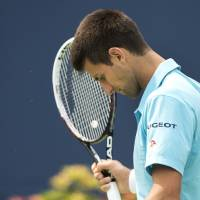 Photo - Novak Djokovic, of Serbia, looks down while playing against Jo-Wilfried Tsonga, of France, in a men's third round match at the Rogers Cup tennis tournament action in Toronto Thursday, Aug. 7, 2014. (AP Photo/The Canadian Press, Nathan Denette)