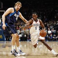 Photo - Oklahoma City's Kyle Weaver (5) drives past Dirk Nowitzki (41) of Dallas in the first half during the NBA basketball game between the Dallas Mavericks and the Oklahoma City Thunder at the Ford Center in Oklahoma City, March 2, 2009. BY NATE BILLINGS, THE OKLAHOMAN ORG XMIT: KOD