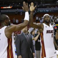 Photo - Miami Heat small forward LeBron James (6) is congratulated by  Dwyane Wade (3) after defeated the Indiana Pacers in Game 1 in their NBA basketball Eastern Conference finals playoff series, Wednesday, May 22, 2013 in Miami. The Heat won 103-102 in overtime. (AP Photo/Lynne Sladky)