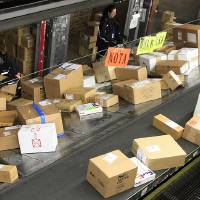 Photo - FILE - In this Dec. 11, 2012 file photo, FedEx workers sort packages at the Oakland Regional Sort Facility in Oakland, Calif. A storm bringing heavy winds and snow to much of the Midwest on Thursday, Dec. 20 — the heaviest shipping day of the year — could mean that some packages might not make it under the tree in time for Christmas.  (AP Photo/Ben Margot, File)