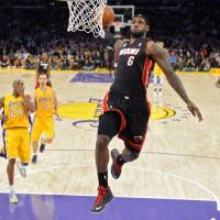 Photo - Miami Heat forward LeBron James (6) goes up for a dunk ahead of Los Angeles Lakers guard Kobe Bryant (24), guard Steve Nash (10) and forward Metta World Peace (15) during the first half of their NBA basketball game, Thursday, Jan. 17, 2013, in Los Angeles. (AP Photo/Mark J. Terrill)