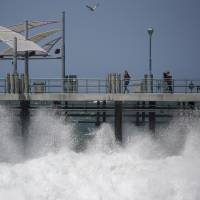 Photo - Waves hit the Redondo Beach Pier in Redondo Beach, Calif., Monday, April 8, 2013. Strong winds have begun raking parts of Southern California. The National Weather Service says the gusty northwest-to-north winds will become widespread across the region Monday and continue into the night.(AP Photo/Jae C. Hong)