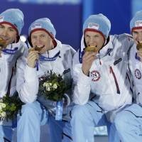 Photo - The team from Norway, who won the gold medal in the team Gundersen large hill Nordic combined competition, bite their medals at the 2014 Winter Olympics, Thursday, Feb. 20, 2014, in Sochi, Russia. (AP Photo/Morry Gash)