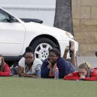 Photo - University of Central Florida students wait outside the college sports arena after explosive devices were found in a nearby dorm, Monday, March 18, 2013, in Orlando, Fla. The campus was closed and classes were postponed until noon. (AP Photo/John Raoux)