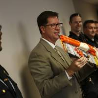 Photo - Norman police Capt. Darry Stacy is presented with a going-away gift at a retirement reception Friday. PHOTOS BY GARETT FISBECK, THE OKLAHOMAN