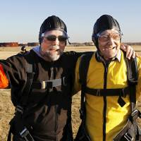 Photo - Warren Crawford, right, and his son Steve Crawford, celebrate after sky diving Saturday at Oklahoma Skydiving Center in Cushing. Photo by Jim Beckel, The Oklahoman